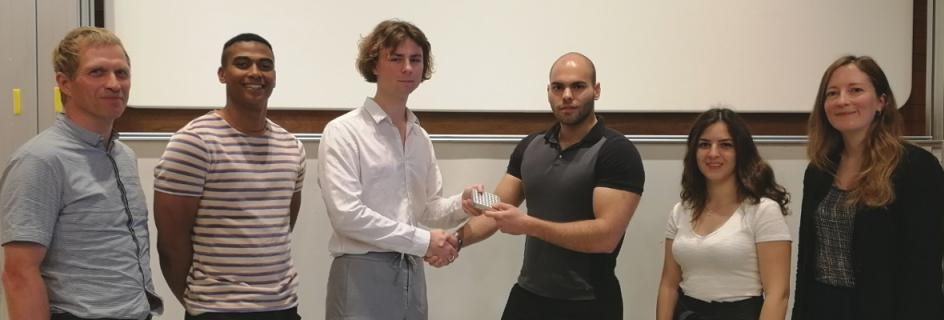 Winner of the Two-Minute Project Presentation event, Eduards Berzins (third from left) is presented with prize by PhD student Evangelos Kafantaris, alongside runners-up, Courtney Blain (second from left) and Doga Satir (second from right) and other judging panel members, Professor Tim Stratford and Naomi Imms