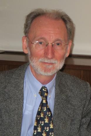 Atholl Hay, smiling portrait photograph, spectacles, grey hair and beard, wearing a grey woolen suit, blue shirt and patterned tie