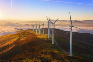 Wind turbines on a mountainous ridge in the setting sun