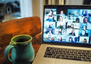 view of laptop on desk with video call panels on monitor and coffee cup beside laptop on desk