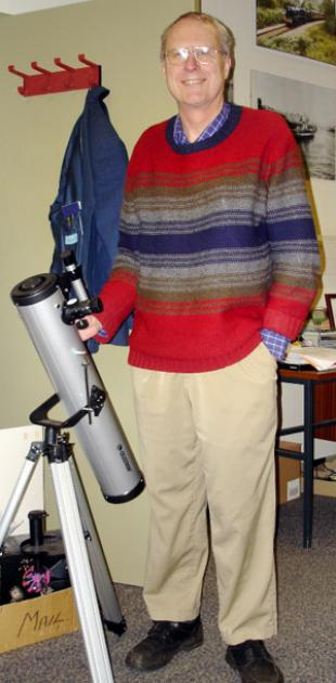 Professor Jim Hough in a red, blue and grey jumper, standing with telescope