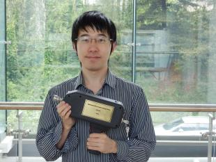 Picture of Di Wu with his prize - A model of the experimental instrument