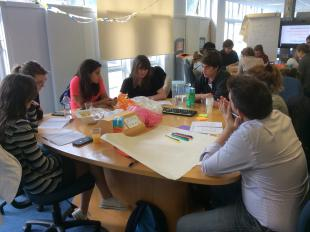 Engineering Students gathered around a table discussing the big issue: How do we collect plastic waste?