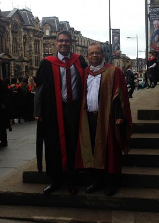 Francesc and Pankaj, in academic gowns, standing on the steps of the Museum of Scotland, Chambers Street, Edinburgh