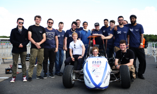 Edinburgh University Formula Student team photo, students standing behind car on race track