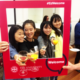 International postgraduate students posing for pictures with University of Edinburgh #edwelcome red picture frame