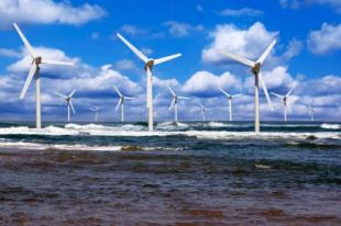Windfarm with several wind turbines pictured with countryside in foreground and blue sky and clouds in the background
