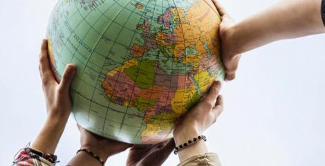 Several people connecting hands on a globe