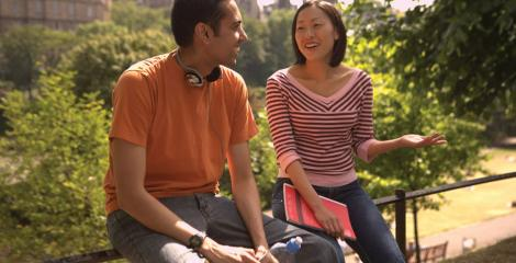 Students talking and laughing while sitting outdoors