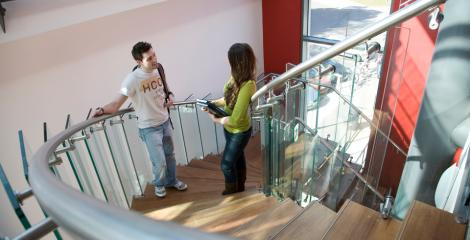 Student and supervisor in discussion on stairway