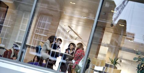 Students in discussion around a table, photo taken from outside building, looking through large glass windows