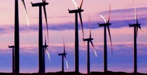 Landscape image of wind turbines, silhoutted against a pink and purple sunset